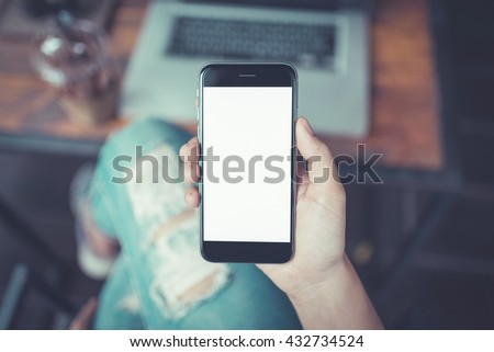 girl using smartphone in cafe. hand holding smartphone white screen. black color smartphone vintage tone. - stock photo