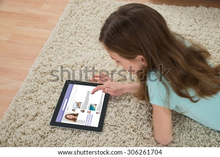 Girl Using Social Networking Site On Digital Tablet At Home - stock photo