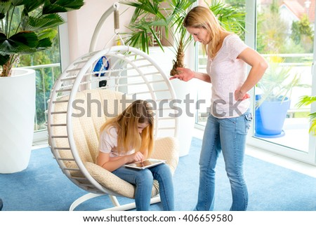 girl using too much her tablet computer and her mother is angry - stock photo