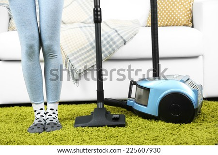 Girl vacuuming in room - stock photo