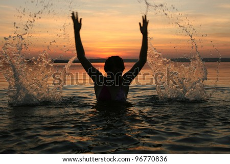 girl very splashing in the water at the beach creating many splashes over their heads against the backdrop of setting sun - stock photo