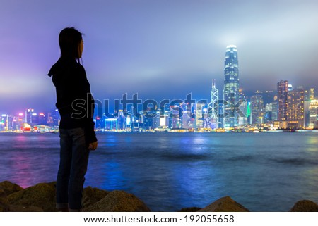 Girl viewing Hong Kong skyline at night - stock photo