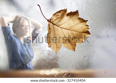 Girl waiting by the window autumn evening.  - stock photo