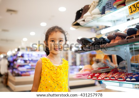 Girl waiting for buy shoes on shelves of shop