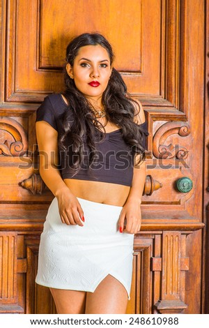 Girl waiting for you. Dressing in a black, short sleeve top, white short fit skirt, a young pretty lady with long curly hair is standing by an old fashion style door, charmingly looking at you.  - stock photo