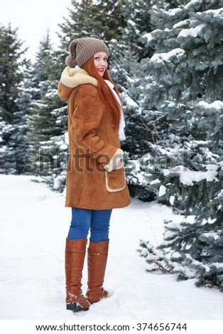 Girl walk in winter park at day. Snowy fir trees. Redhead woman full length. - stock photo