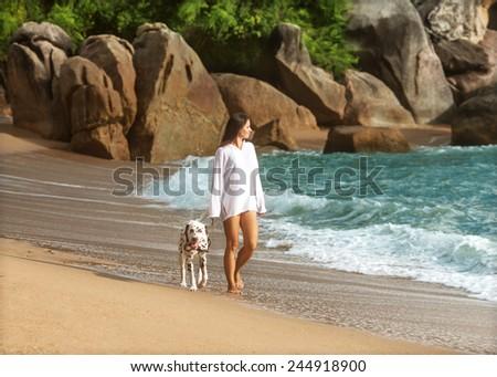 girl walk on the beach with the dog Dalmatian  - stock photo