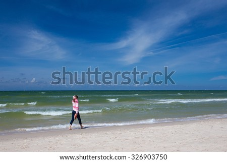 girl walking along an empty beach at sunny windy day
