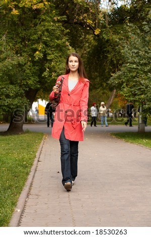 Girl walking along footpath and eating chocolate ice cream
