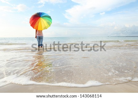 Girl walking along the beach with colour full umbella.