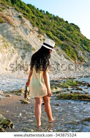Girl walking along the seashore - stock photo