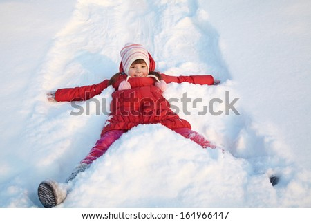 girl walking around outdoors in the winter, playing with snow