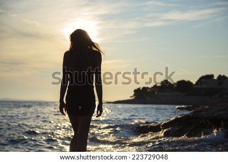 girl walking by the sea at sunset - stock photo