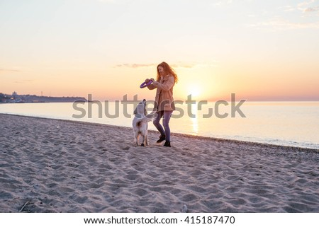 girl walking dog on beach during sunset