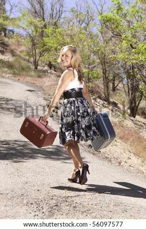 Girl walking down road carrying suitcases and looking back over her shoulder. - stock photo