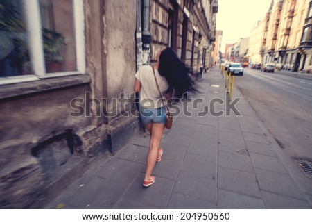 Girl walking in the city, blurry