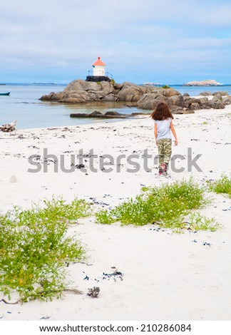 Girl walking on a beach towards lighthouse - stock photo