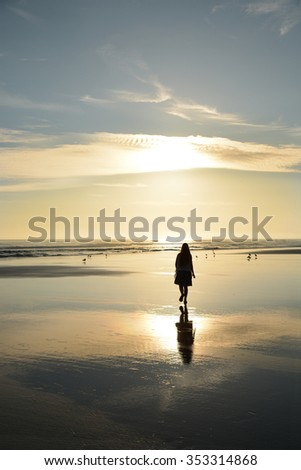Girl walking on a beautiful golden beach, Daytona Beach, Florida. - stock photo