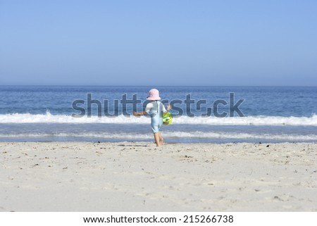 Girl (3-5) walking on sandy beach with bucket and spade, rear view, sea in background