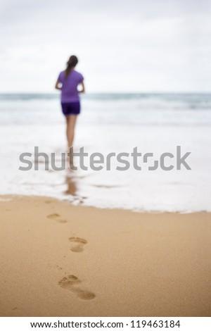 Girl walking on the beach. Selective focus. - stock photo