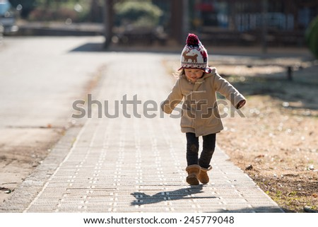 Girl walking on the sidewalk - stock photo