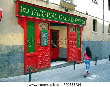 Girl walking past one of numerous taverns of Madrid-June 12,2005 - stock photo