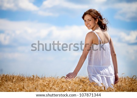 Girl walking thought golden wheat field - stock photo