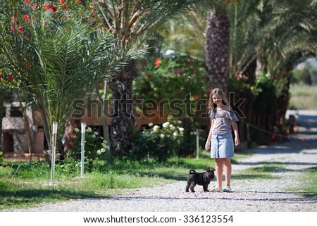 Girl walking with dog in garden