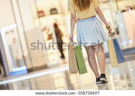 Girl walking with shopping bags in her hands, view from the back