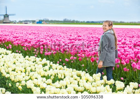 Girl walks between of the colorful tulips field