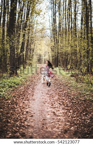 Girl walks in the woods with the dog Laika
