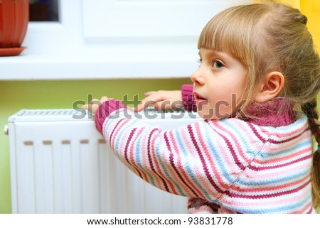 Girl warm one's hands near radiator at home. - stock photo