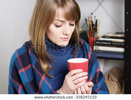 Girl warms. Home comfort concept. Cold and sick woman.  Beautiful blond woman sitting on a comfortable couch,wrapped in blanket and holding mug of tea.  - stock photo