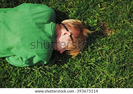 girl was tired and lay down to relax on the grass near the road - stock photo
