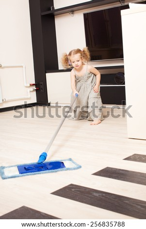 Girl washes a floor mop. Helps the child to do housework - stock photo