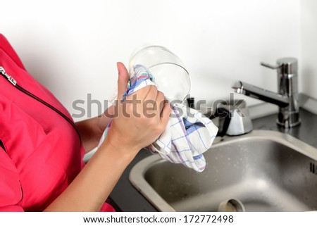 girl washes dishes by hand in the sink