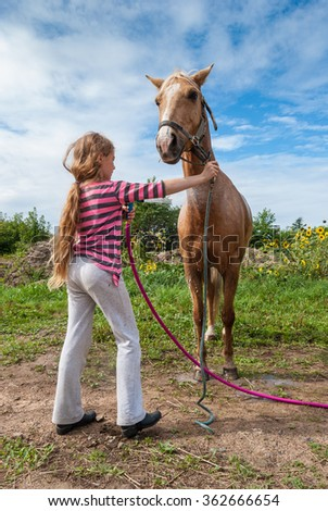 Girl washing a horse with a hose on a farm