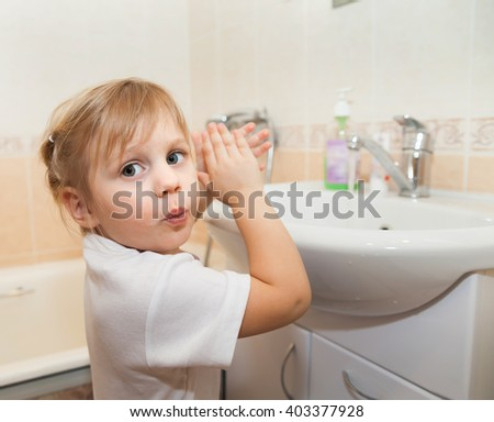 girl washing  hands   by   sink in   bathroom.