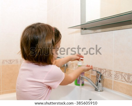 girl washing her hands with soap by   sink in   bathroom.