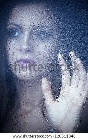 Girl watching through the window after a rain. Portrait.