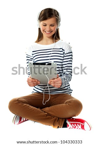 Girl watching video on tablet pc with headphones attached to it