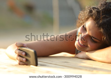 Girl watching videos or social media in a smart phone relaxing in a park at sunset - stock photo