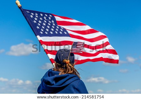Girl waving a big American flag against a blue sky with puffy white clouds. She also has a small flag stuck in her ponytail.  - stock photo