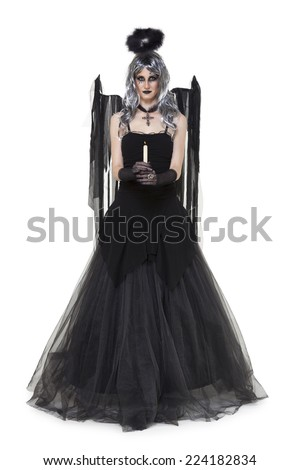 Girl wearing a black halloween costume with candle on white - stock photo
