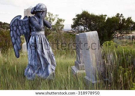 Girl wearing a home made life like angel costume in an old grave yard
