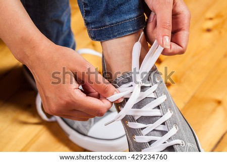 Girl wearing a pair of sneakers at home. A sneaker is untied