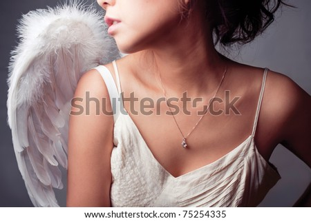 Girl wearing a white top with wings.