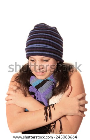 Girl wearing a wool hat and scarf but bare sleeves, holding herself as if cold or freezing. - stock photo