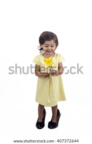 Girl wearing adult shoes and with a daffodil isolated on white background