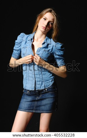girl wearing blue jeans shorts and the black top over black background